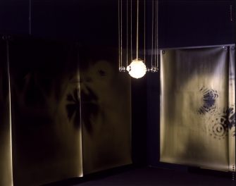 Bill Jones, Soul Catcher, 1989, silver prints on gold paper, 13 prints 139 x 193 cm, 55 x 76 inches each, steel, magnets, crystal lamp, eyeglasses, Installation view The Brooklyn Museum.